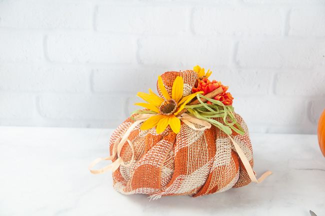 A plaid burlap fabric pumpkin with fall florals and ribbons