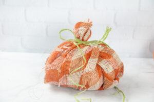 A plaid burlap pumpkin with raffia and ribbon tied around the stem.
