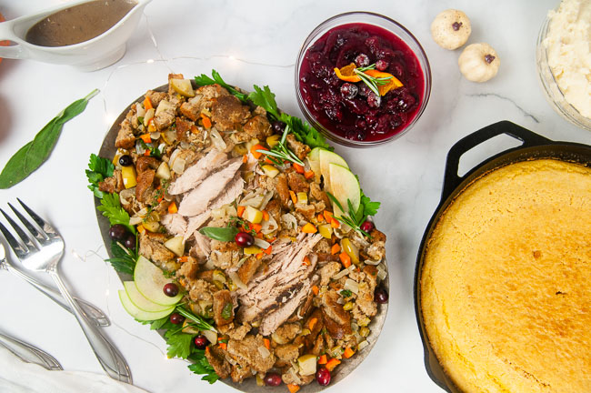 No turkey dinner is complete without cranberry sauce! A silver serving platter loaded with turkey and stuffing with a bowl of cranberry sauce on the side.