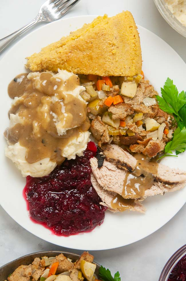 No turkey dinner is complete without cranberry sauce! A white plate loaded with turkey, stuffing, gravy, cornbread and cranberry sauce.