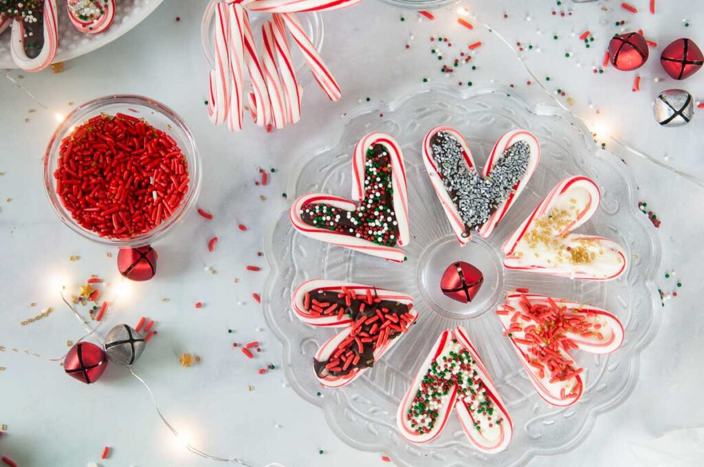 A festive spread featuring easy candy cane hearts on a white counter with sprinkles and candy canes