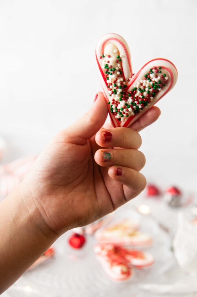 A child's hand holds a candy cane heart filled with chocolate and sprinkles