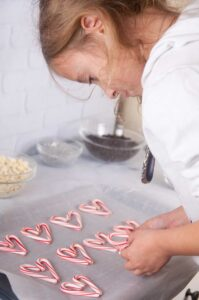 A little girl arranging candy canes like hearts on a cookie sheet