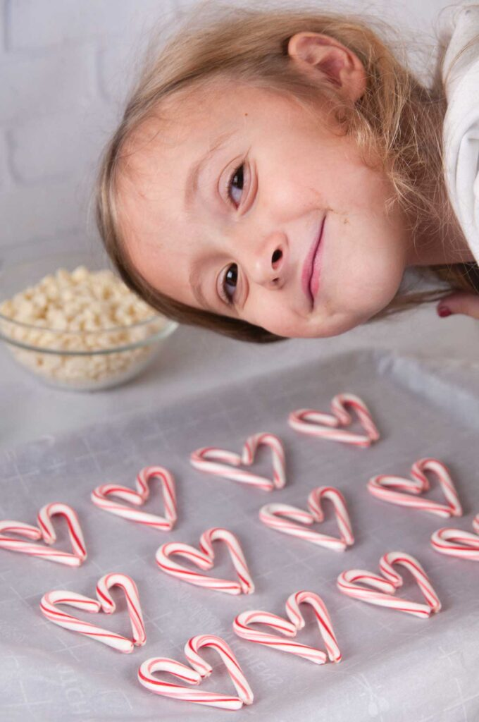 A little girl smiling over a tray of candy cane hearts