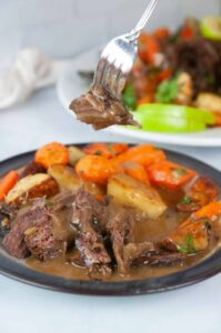 A forkful of tender Instant Pot Roast beef is slathered in apple cider gravy and served with roasted carrots and potatoes.