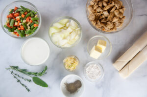 Ingredients for mini chicken pot pies in small bowls: frozen vegetables, half and half, diced onion, spices, butter, flour, cooked chicken and pie crust