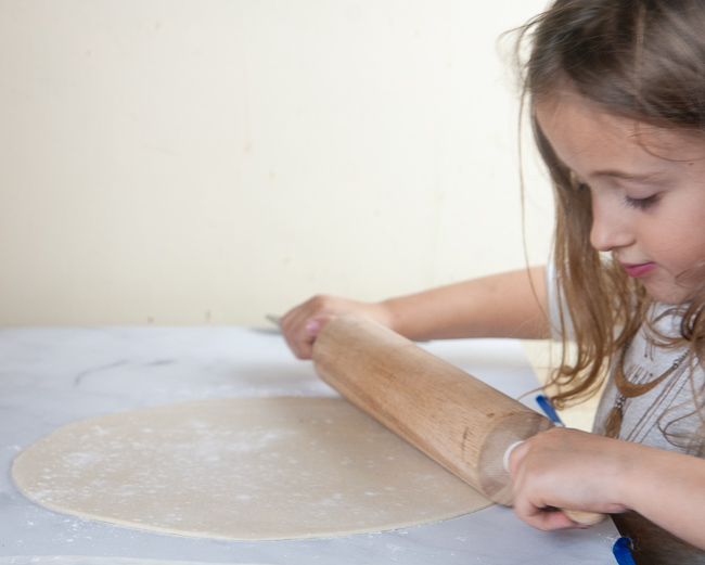 A child rolling out pie crust