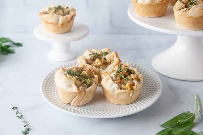 Mini chicken pot pies on white platters in a white kitchen. These pot pies are a kid and freezer friendly way to use up leftover chicken or turkey.