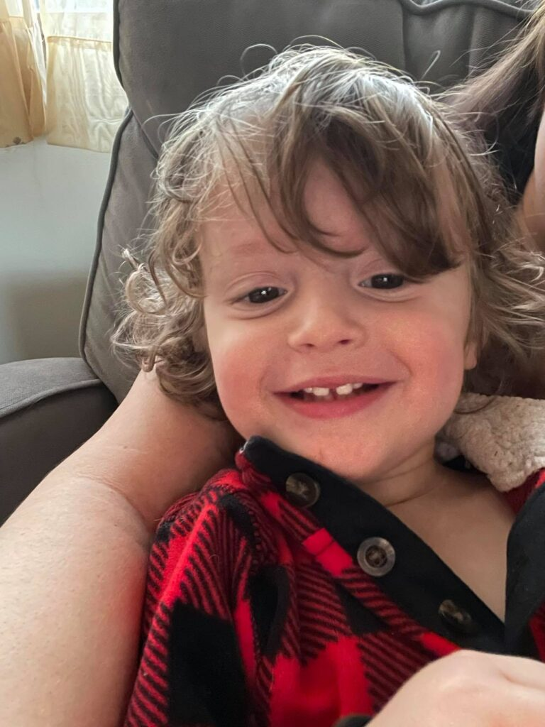 toddler boy smiling with hair in his eyes