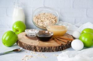 Ingredients for baked oatmeal with apples: apples, oats, eggs, cinnamon, vanilla, milk, applesauce, coconut oil, eggs