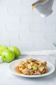 Baked Apple Oatmeal drizzled with maple syrup makes a hearty, wholesome breakfast.