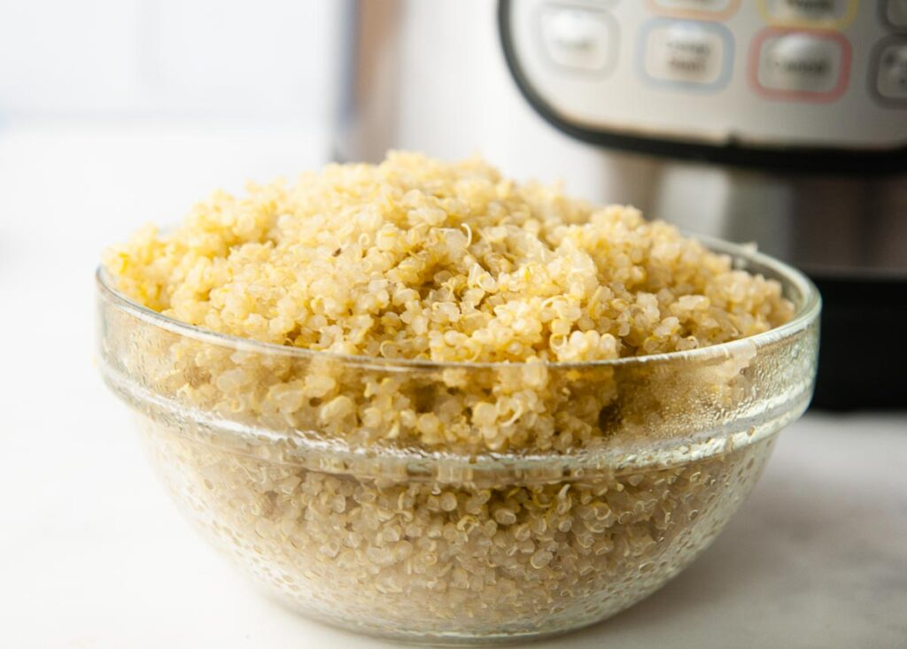 Making quinoa in the Instant Pot is perfect for meal prep. A bowl of quinoa in front of the pressure cooker.