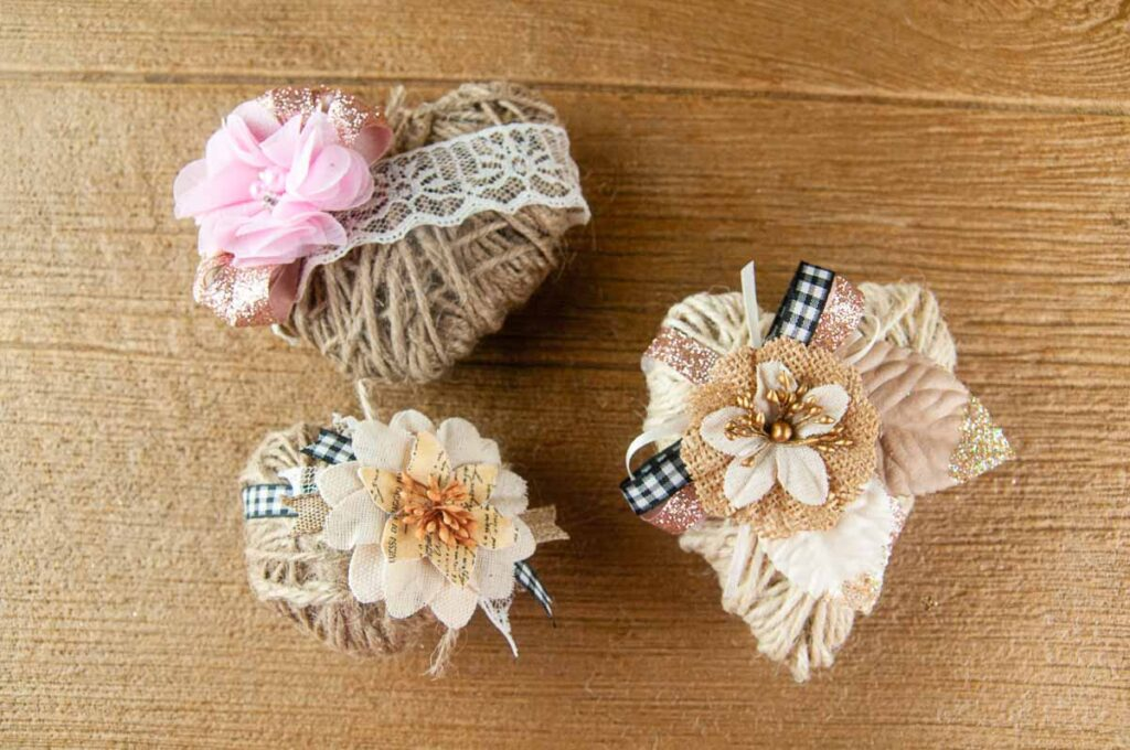 Three Different DIY Twine Hearts on Wood. Change up the embellishment to suit different occasions and make rustic farmhouse decor for weddings, Valentine's Day, spring or even Christmas.