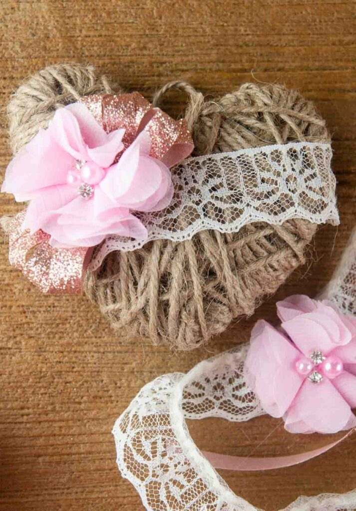 A DIY twine heart craft is a lovely decoration for Valentine's Day, spring, weddings or even Christmas. The rustic farmhouse decor is shown with lace and floral embellishments on wood.