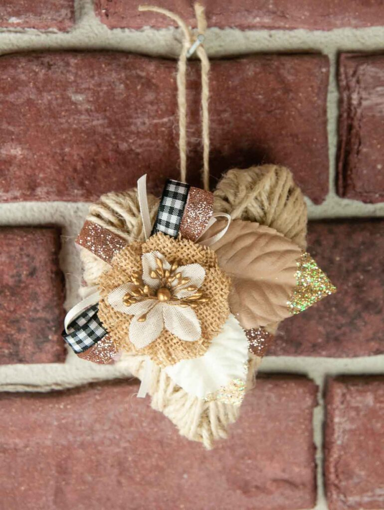 Embellished twine heart hanging against a brick wall.