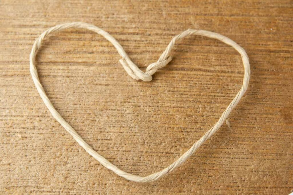 Shape the floral wire stem into a heart shape. Floral wire stem shaped like a heart on wood.