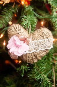 A twine heart hanging from a Christmas tree.