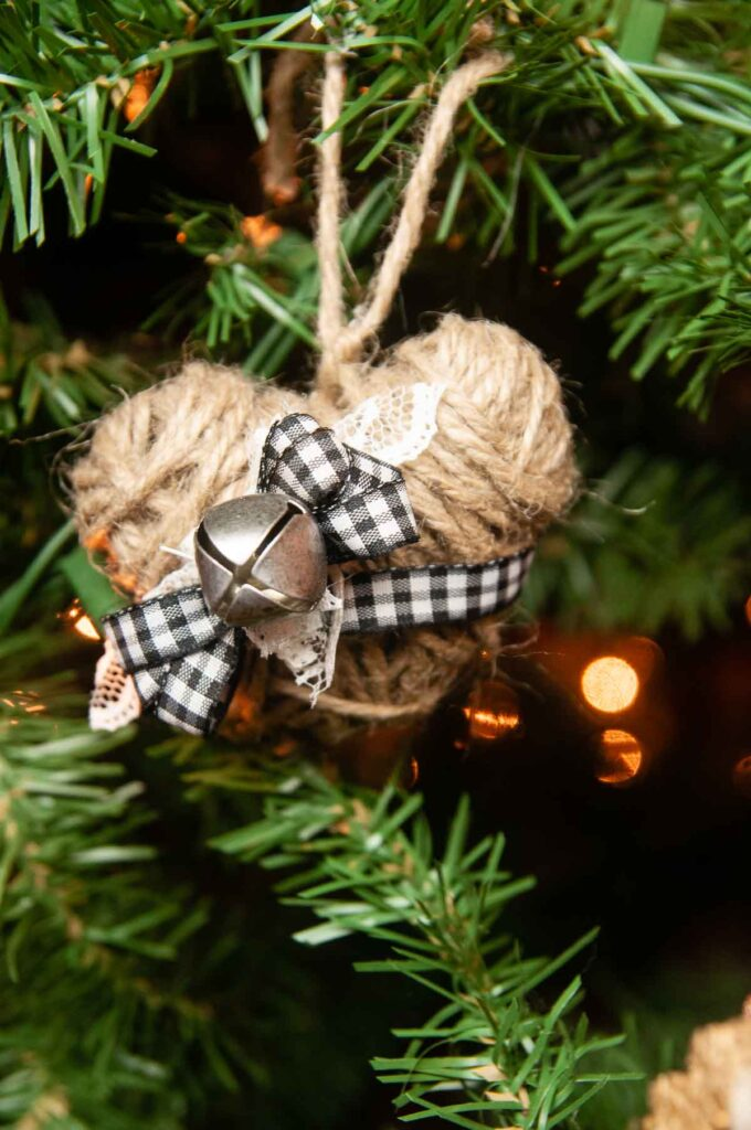 A twine heart decorated for Christmas with a jingle bell and buffalo plaid bow on a Christmas tree.