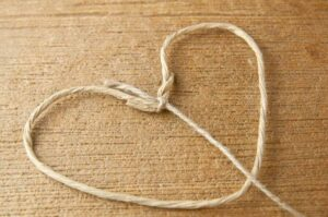 A floral wire heart shaped frame with twine tied to the v of the heart
