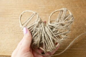 A female hand holding a floral wire heart frame being wrapped in twine.