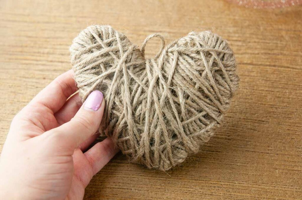 A hand holding a DIY twine heart craft done being wrapped in twine but not yet embellished.