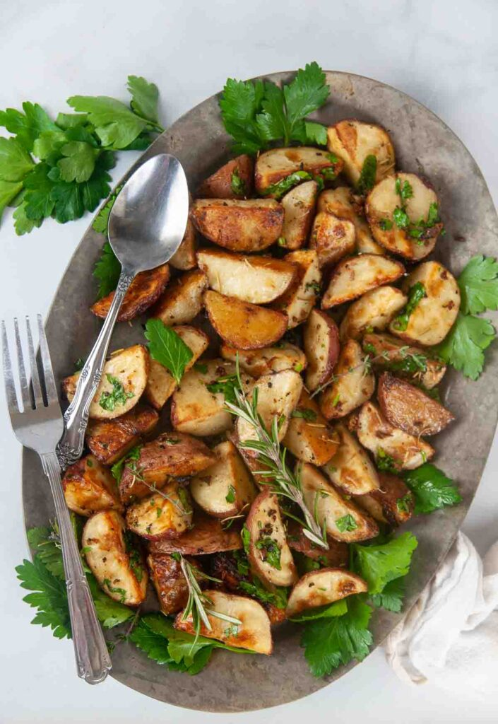 Garlic and Herb Roasted Red Potatoes make a delicious side dish. Shown on a silver serving plate with greens.