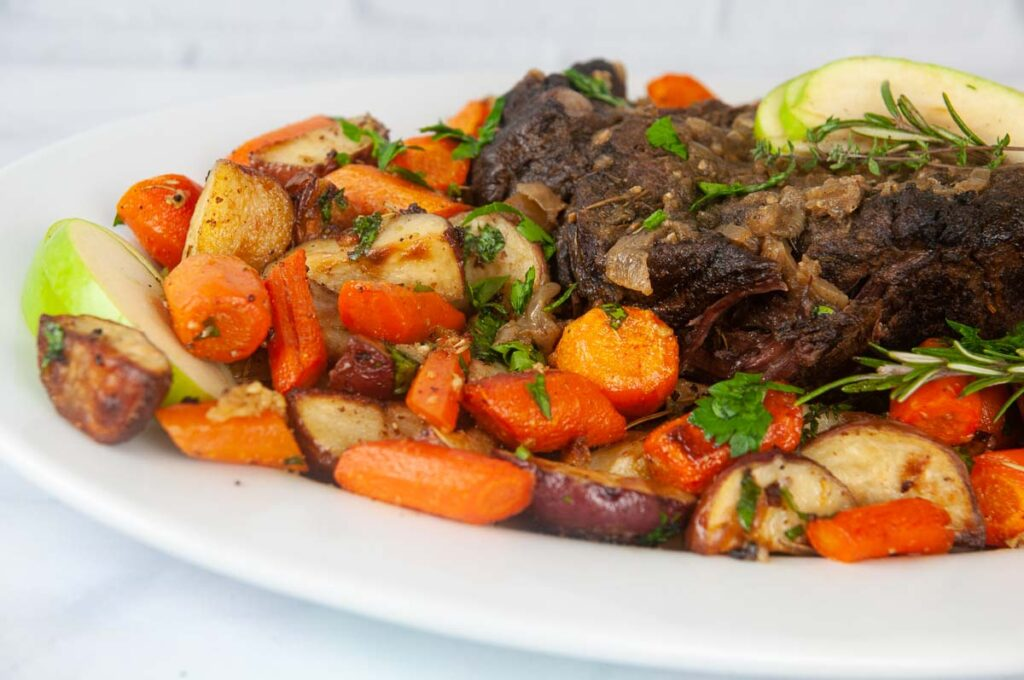 Garlic and Herb Roasted Red Potatoes shown with roasted carrots and roast beef.