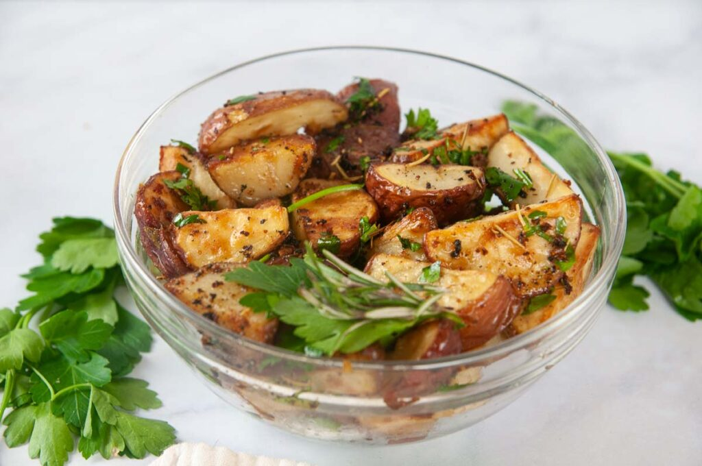 Garlic and Herb Roasted Red Potatoes in a clear glass bowl with lots of fresh herbs