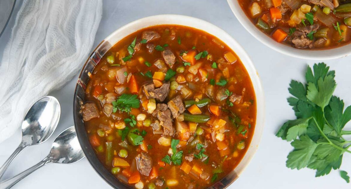 2 bowls of hearty Instant Pot vegetable beef soup ready for a cozy dinner on a white background.