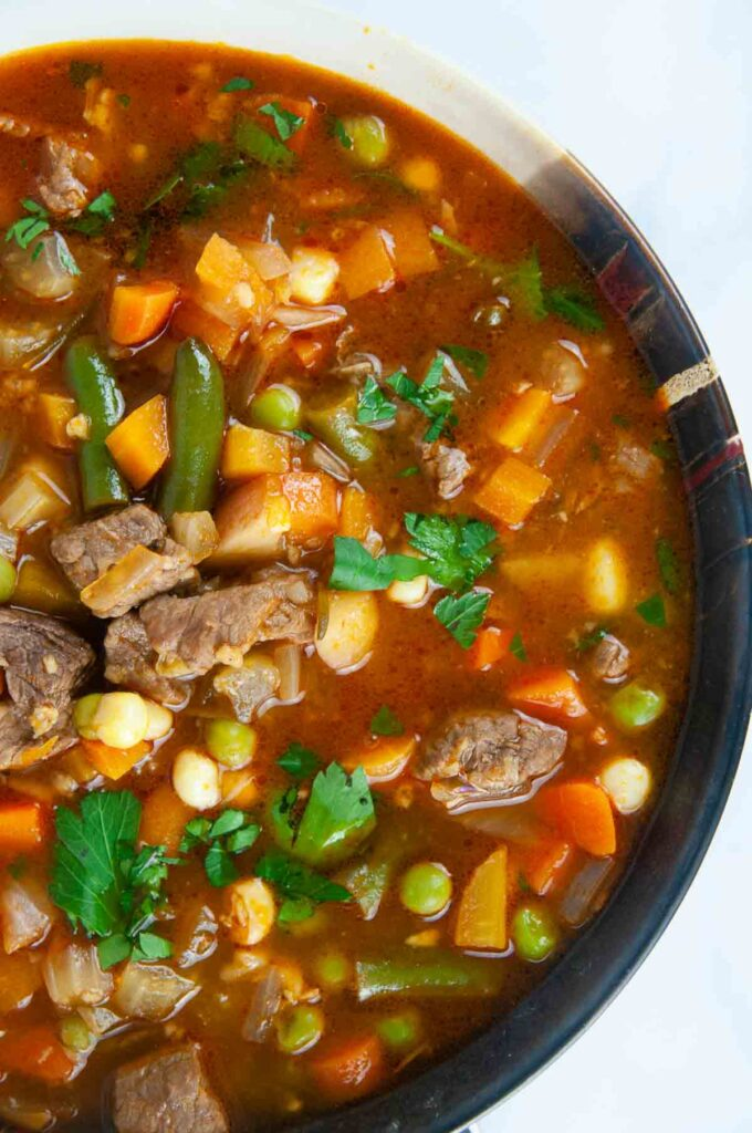 A bowl of hearty Instant Pot vegetable beef soup ready for a cozy dinner on a white background.