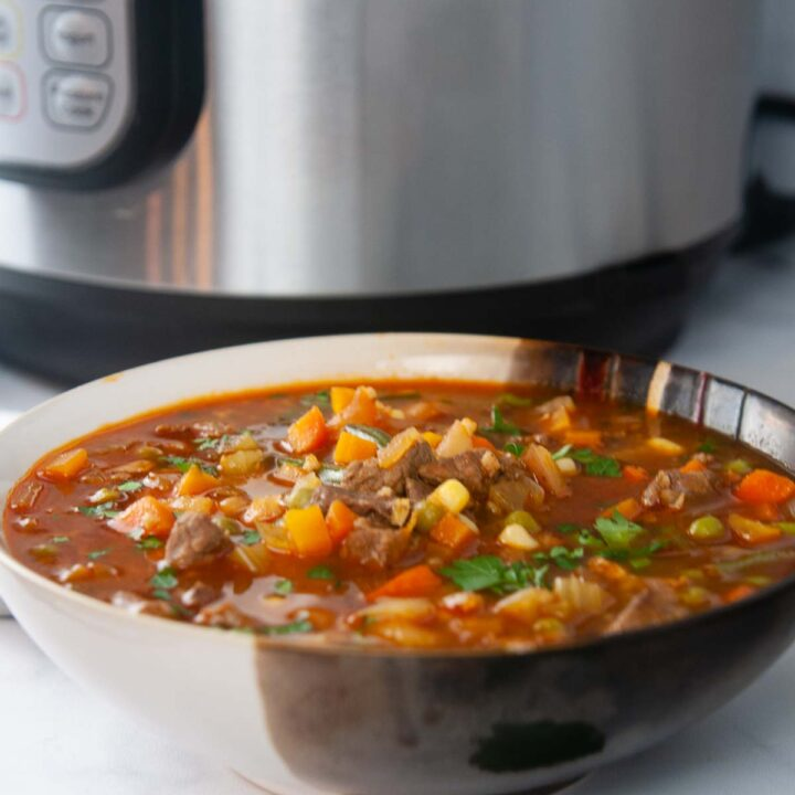 Instnat Pot Vegetable Beef soup is the perfect make ahead dinner. A bowl of it shown in front of the Instant Pot.