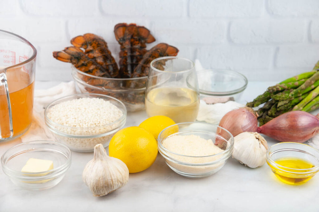 Ingredients needed for lobster risotto: white wine, vegetable broth, butter, olive oil, lobster tails, risotto, Parmesan cheese, garlic cloves, lemon juice, salt, pepper, and shallots.