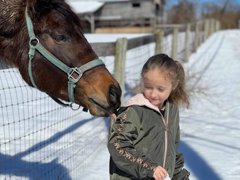 Horse licking a girl's hood in the snow