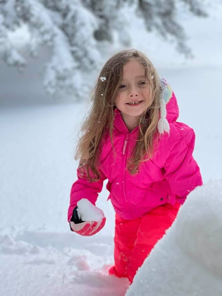 Elementary school girl in pink snow gear playing in deep snow