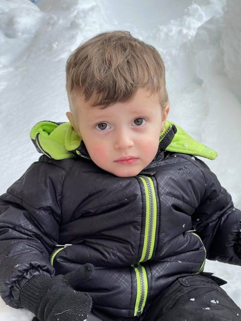 cranky toddler sitting in snow