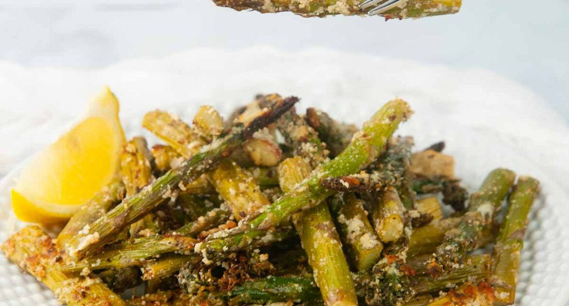 A forkful of air fryer asparagus with parmesan cheese in a white kitchen. It makes the perfect side or light, crispy appetizer.