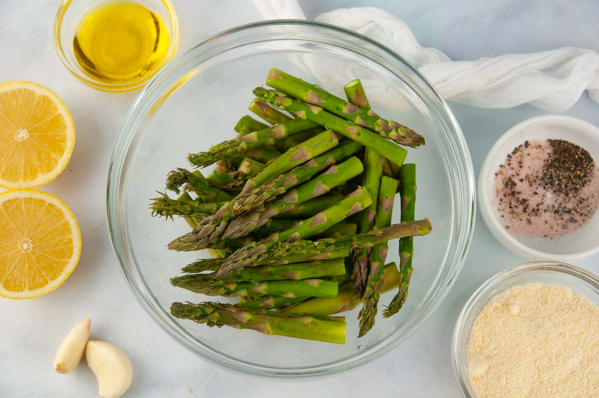 Ingredients for Air Fryer Asparagus: Trimmed asparagus, parmesan cheese, salt and pepper, lemon, olive oil and garlic
