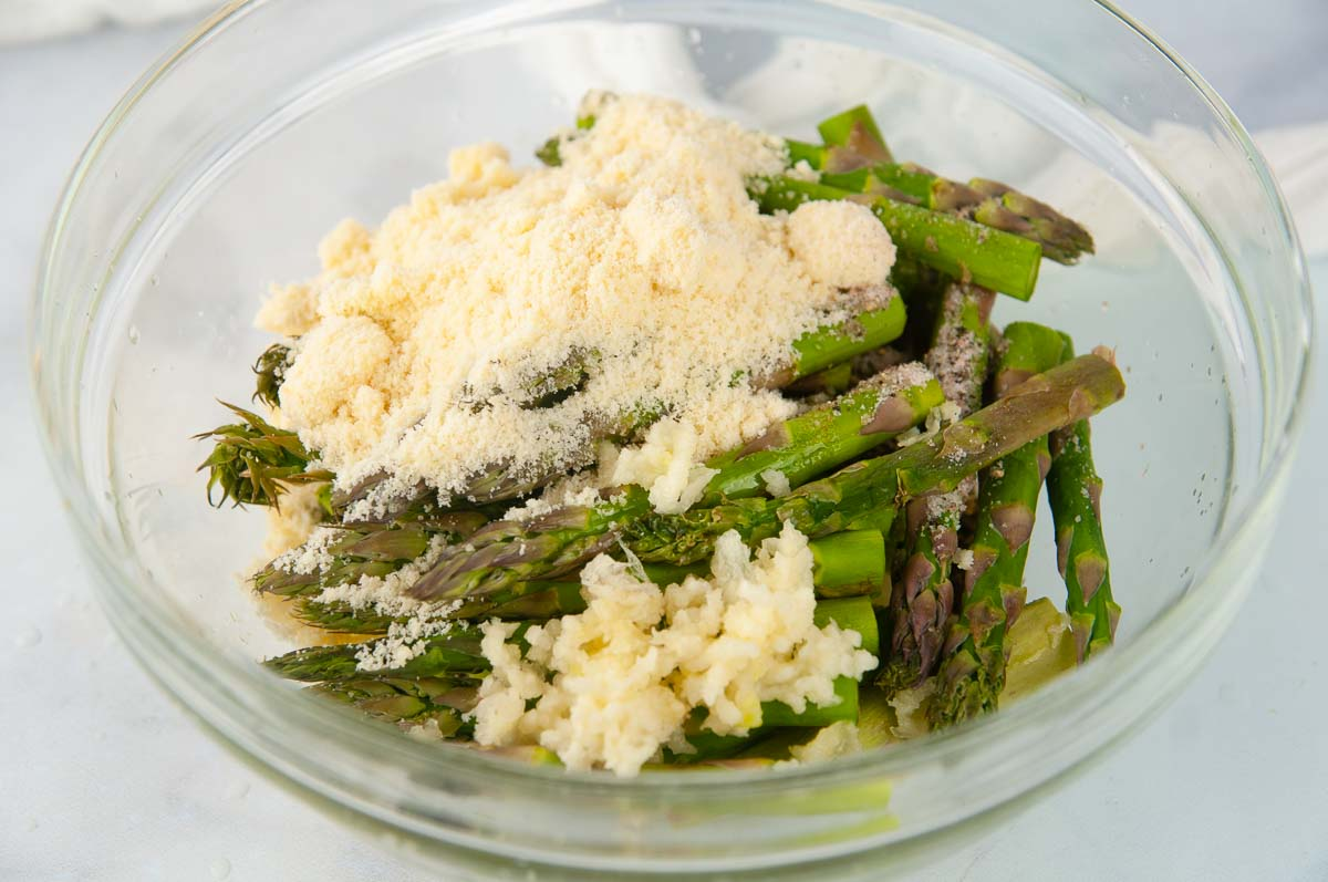 Asparagus in a clear bowl with parmesan cheese, lemon juice, olive oil, and seasoning