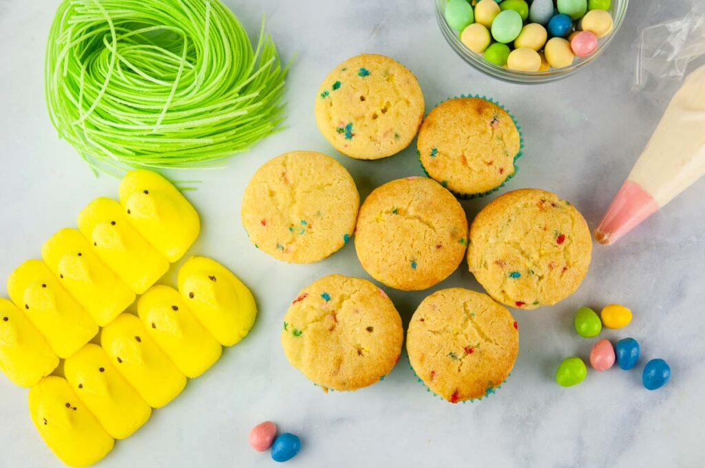 Ingredients for Easter cupcakes: cupcakes, buttercream, chick peeps, edible Easter grass, candy coated eggs