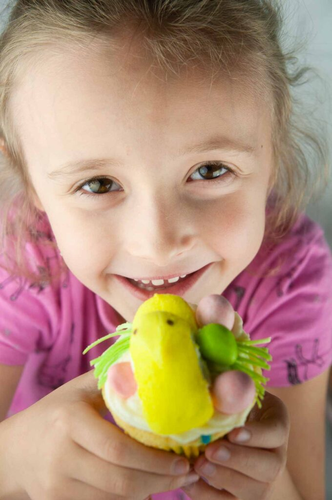 Little girl holding a decorated Easter cupcake and smiling