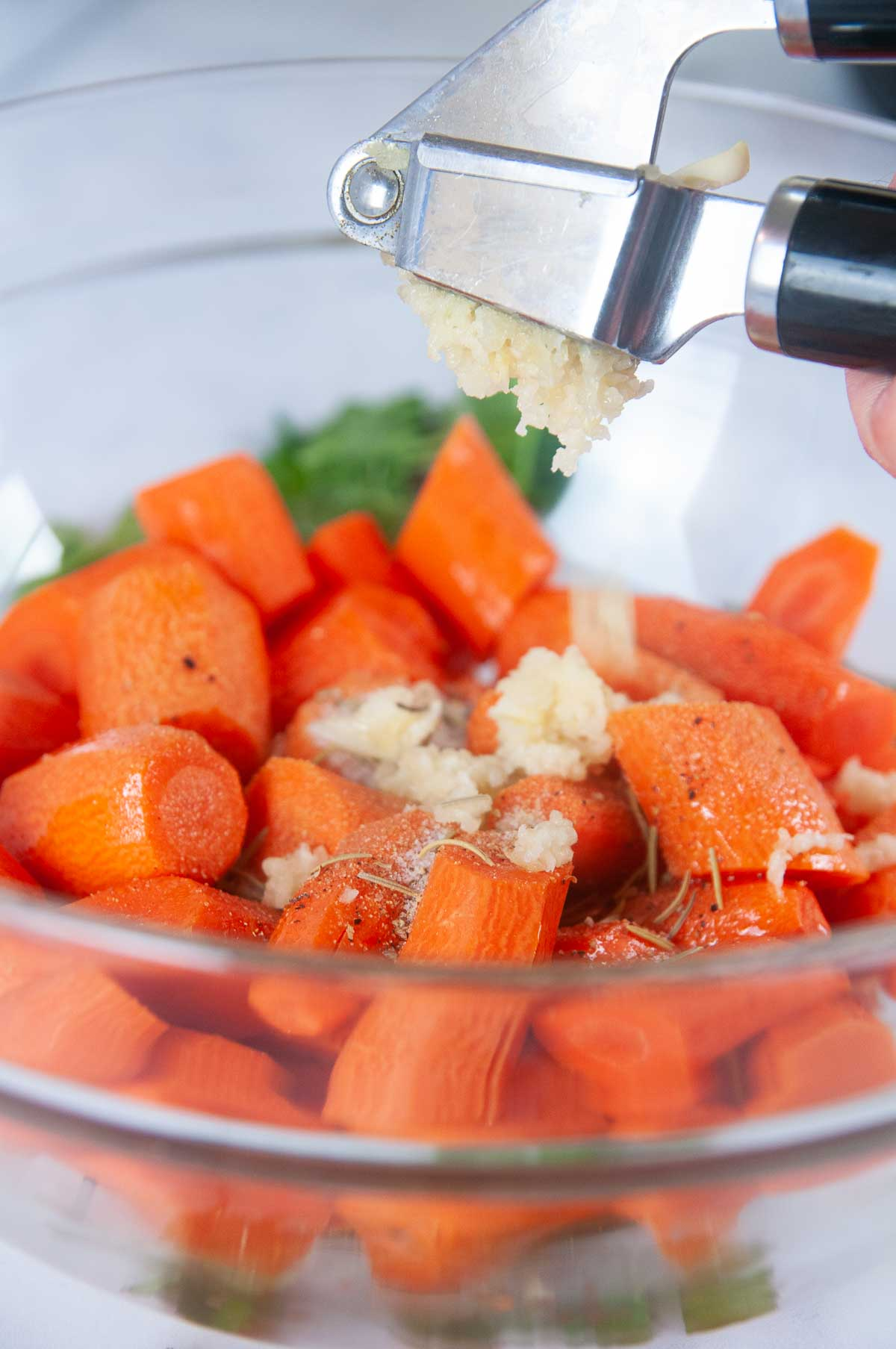 Season the carrots with fresh pressed garlic and herbs.