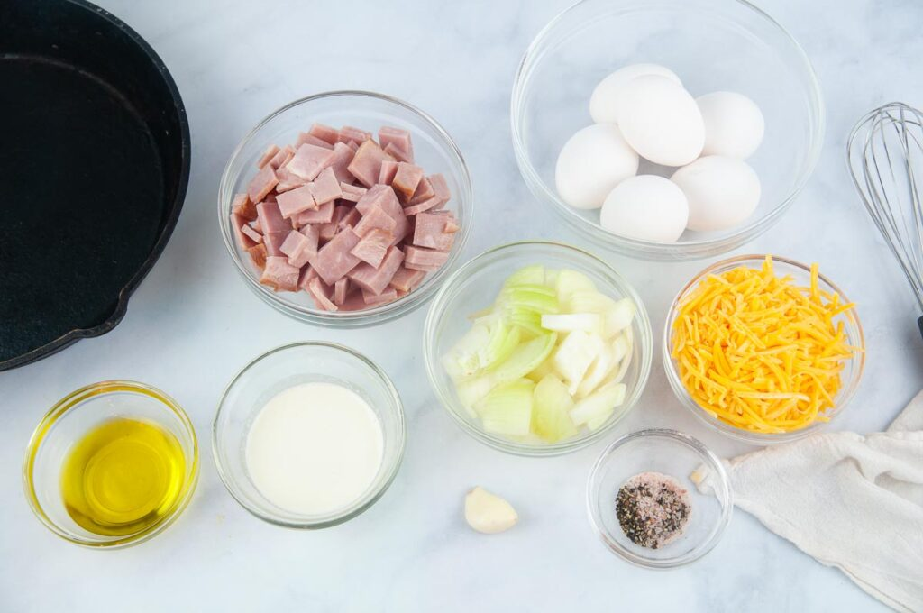 Ingredients for ham and cheese frittata on a white counter in bowls. Ingredients: chopped ham, heavy cream, olive oil, eggs, onion, cheese, garlic, salt and pepper