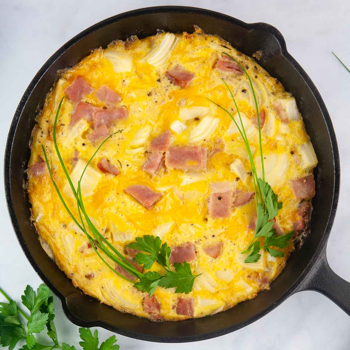Ham and Cheese Frittata is a kind of crustless quiche shown in a cast iron skillet that makes a lovely breakfast or brunch>