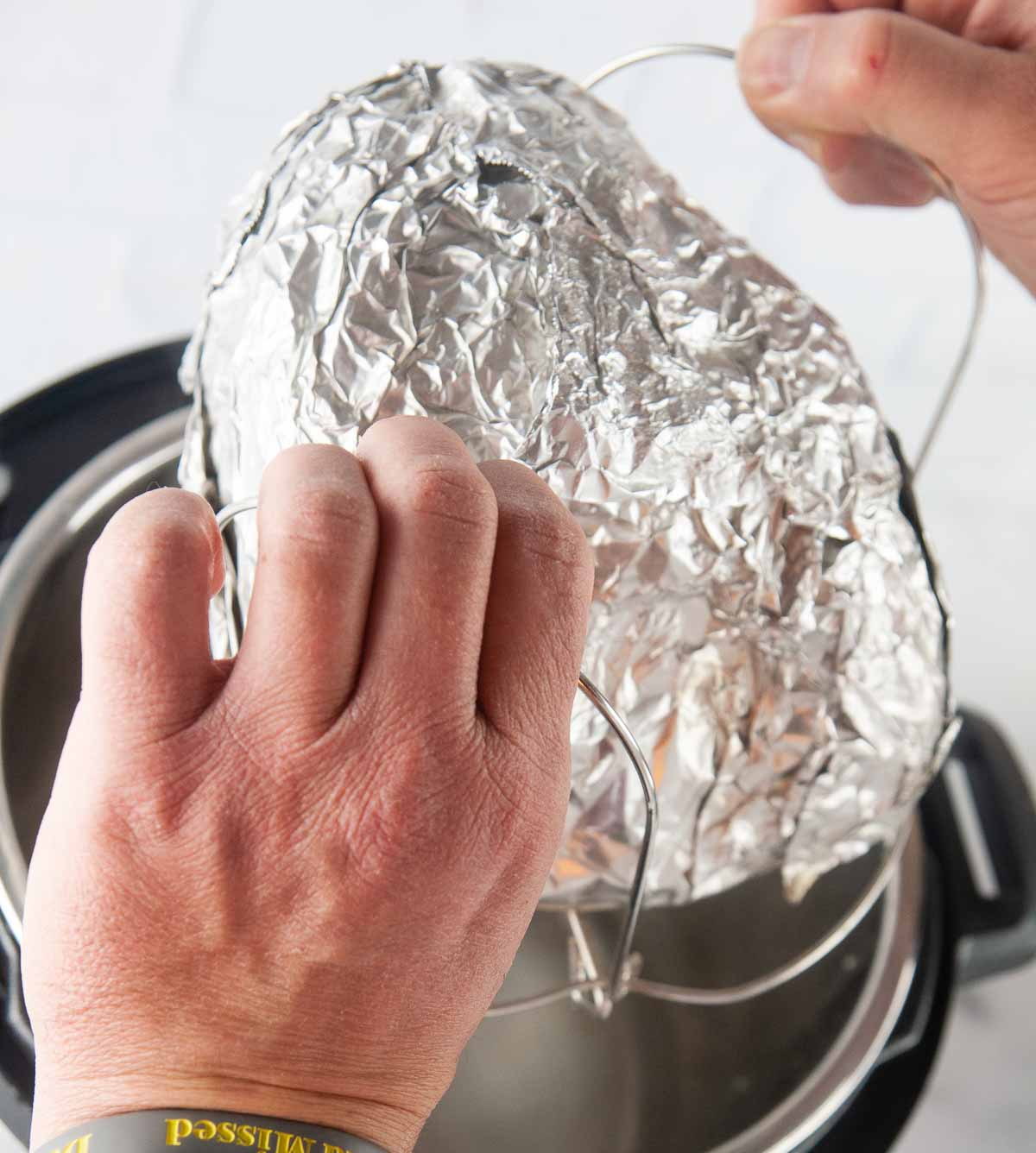 Put the foil wrapped ham on the trivet and carefully put in the Instant Pot.