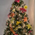 a christmas tree decorated for spring with pink and yellow flowers, butterflies, and burlap