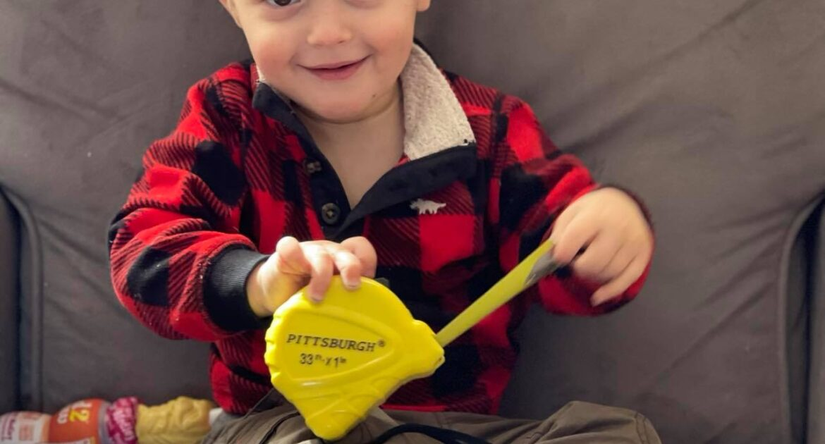 toddler holding a measuring tape