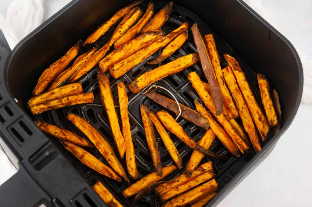 Cooked sweet potato fries in an air fryer basket