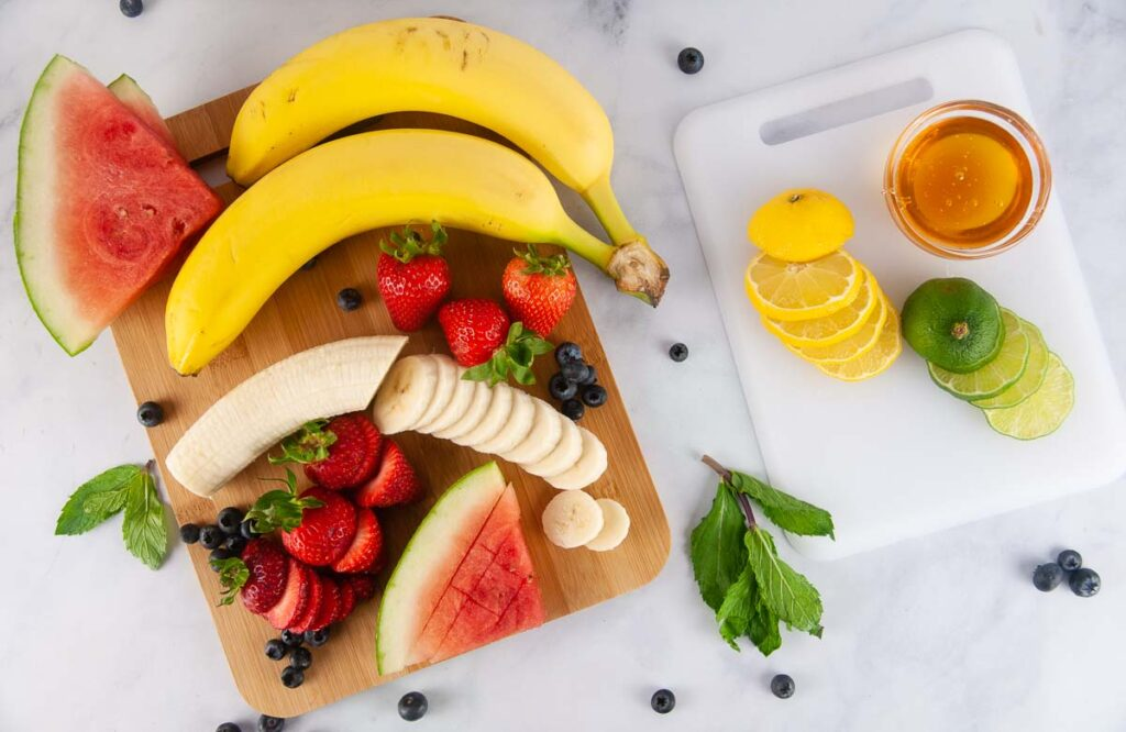 Ingredients for Red, White and Blue Fruit Salad: bananas, strawberries, blueberries, watermelon, lemon juice, lime juice and honey