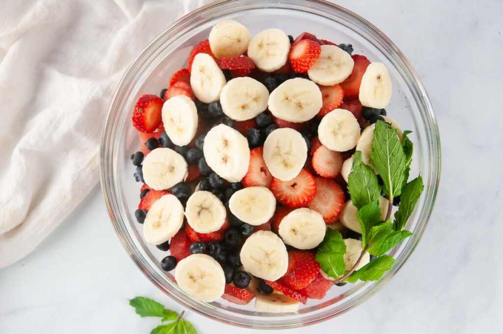 Add the sliced, cleaned fruit to a large bowl.