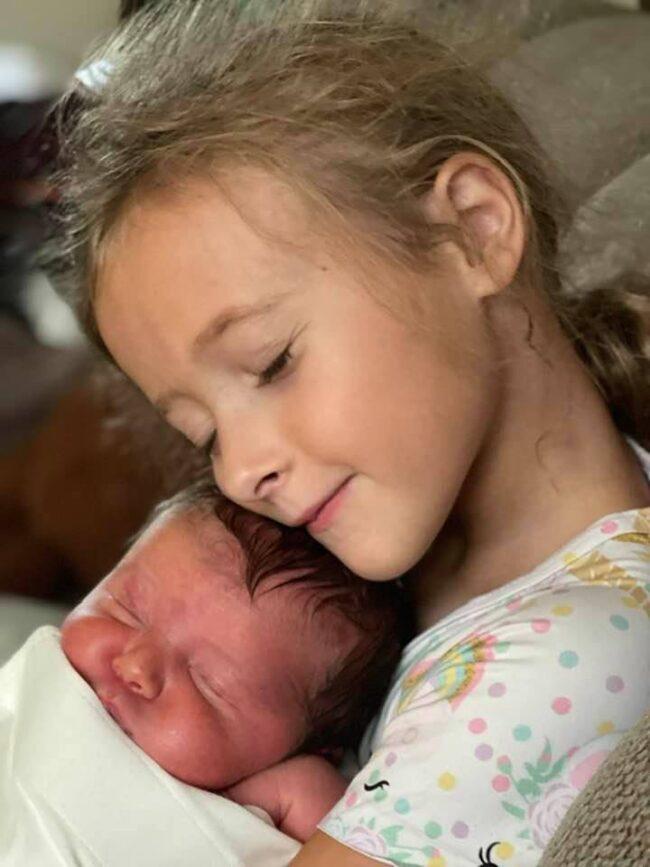 A little girl snuggling a newborn